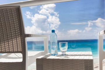 Photo sur Aluminium Dauphins Balcony with plastic bottle of water on table overlooking an oc