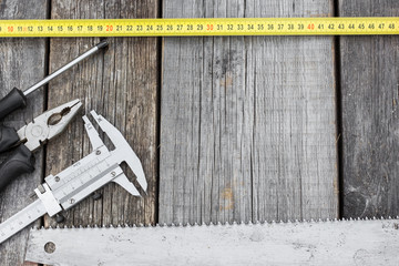 Different construction tools on a wooden background with copy sp