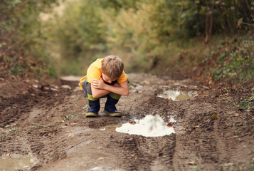 Boy look into the puddle on the country road