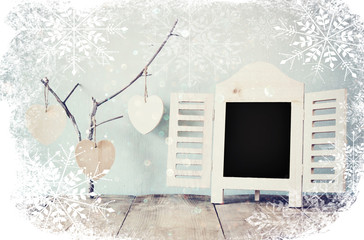 decorative chalkboard frame and wooden hanging hearts over wooden table. ready for text or mockup. retro filtered image with snowflakes overlay