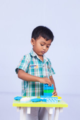 a little asian boy play building brick on white background