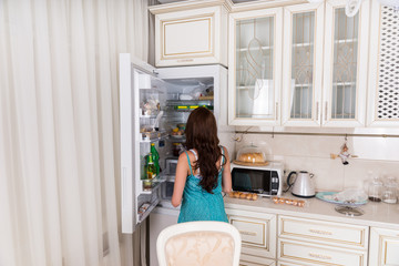 Woman Standing in front of Open Refrigerator