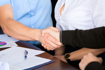 Handshake of two businessmen on the background of the Secretary