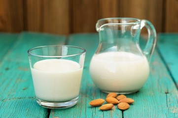 Homemade fresh almond milk in glass jar and glass bowl, with hom