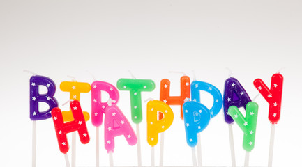 Colorful candles in letters saying Happy Birthday