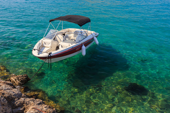 Small white boat floating in clean water near shore
