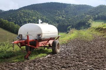 Anhänger mit Wassertank steht auf einer Weide