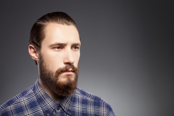 Attractive young man with beard is pensive and sad