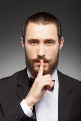 Cheerful young businessman with beard is gesturing