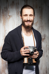 Handsome bearded man is using camera with joy