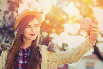 Beautiful teenage girl taking a selfie in park in autumn