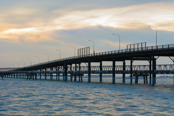 Bridge across the sea and sunset scene.
