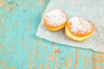 Sweet sugary donuts on rustic table