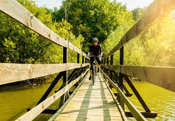 Young biker woman riding a bike in a bridge.
