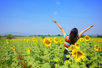 Woman acting relax in the sunflowers field