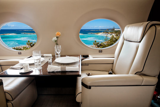 Business jet aiircraft porthole with view of sea and beach resor