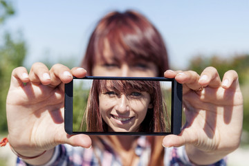 pretty woman with red hair take a selfie with smart phone