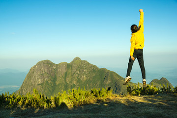 hiker celebrating success on top of a mountain