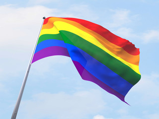 Rainbow flag flying on clear sky.