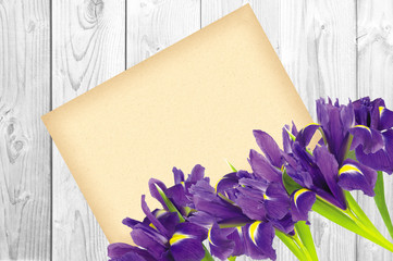 Blueflag or iris flower and greeting card on white wooden backgr