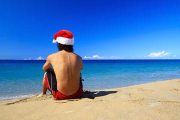 Man in santa claus hat on a beach