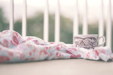 A cup of coffee on a table with a floral pattern fabric and the blurred outside view from a window. Soft colors, blurred image with selective focus on the cup. Relax and good morning concept.