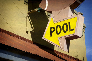 aged and worn vintage photo of pool sign