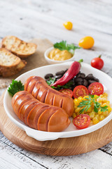 Sausages on the grill with vegetables on a platter