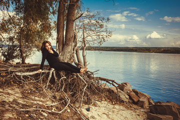 Beautiful young girl sitting on a rock by the river