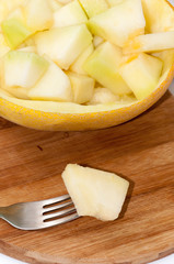 Melon on the fork with slices of melon in the bowl