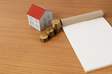 Paper house with coins stack and notepad for Mortgage loans conc