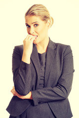 Stressed young woman biting her nails