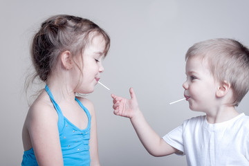 siblings having fun with lollypops - little brother is trying to