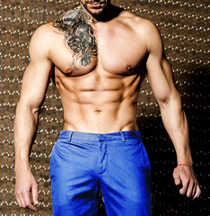 Handsome tattooed man with beautiful muscular body in blue pants
