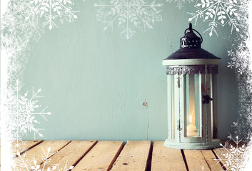 low key image of white wooden vintage lantern with burning candle and tree branches on wooden table. retro filtered image with snowflakes overlay