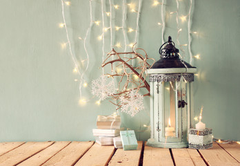 white wooden vintage lantern with burning candle, christmas gifts and tree branches on wooden table. retro filtered image