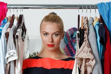 Beautiful thoughtful blonde woman standing inside wardrobe rack
