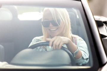 Young cheerful woman riding convertible