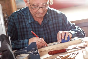 Senior carpenter working in hi workshop