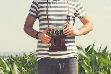 Young hipster man holding retro photo camera.