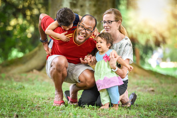 Happy interracial family is being active a day in the park