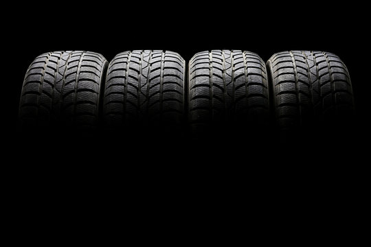 Set of four black car tires lined up horizontally