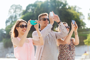 smiling friends with smartphone taking picture