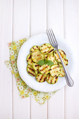 Grilled zucchini in a white plate with a fork decorated with basil