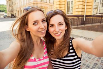 Friends making selfie. Two beautiful young women making selfie p