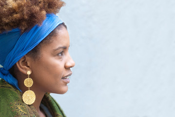 Head shot of young afro american curly woman profile in front of