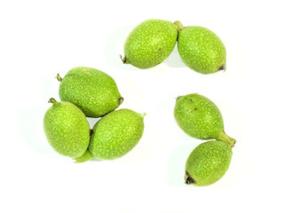 Green seven young walnuts in husks on white background