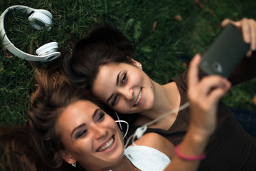 Girlfriends taking picture with smartphone lying on the grass