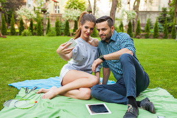 Couple sitting on the blaket, spending nice time and taking selfie.