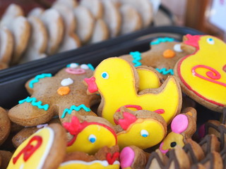 Colorful gingerbread cookies in a shape of small yellow ducks.